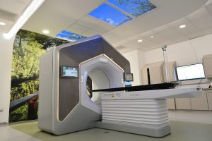 ETHOS radiotherapy machine with mural of local scenery and sky window.